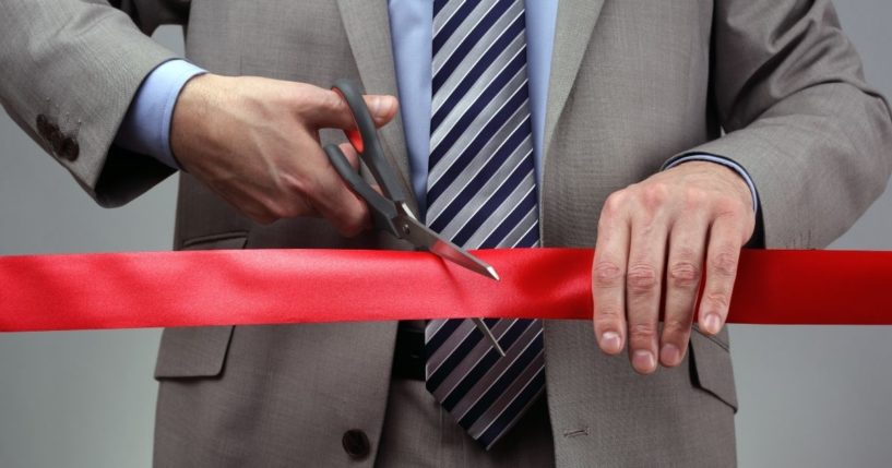 A man is pictured cutting through red tape in the stock image above.