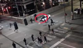 Surveillance footage of an intersection outside the East Precinct from Saturday evening shows a driver's response to antifa protesters blocking off the roadway.