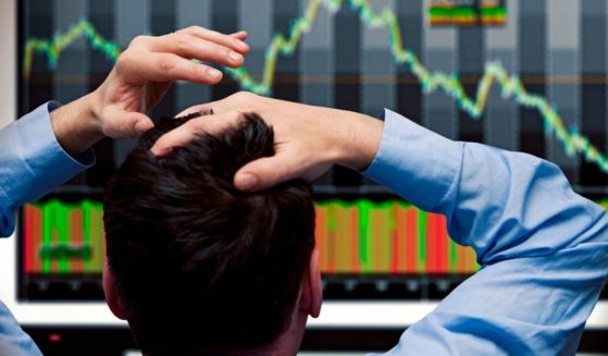 In this stock photo, an investor looks at stock prices dropping on a screen.