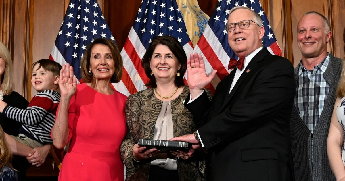 Democratic House Speaker Nancy Pelosi poses during a ceremonial swearing-in with Republican Rep. Ron Wright of Texas and his wife, Susan Wright, on Capitol Hill in Washington during the opening session of the 116th Congress on Jan. 3, 2019.