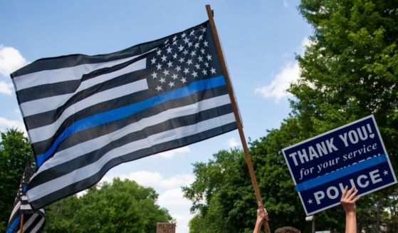 "A demonstrator holds a ""Thin Blue Line"" flag and a sign in support of police during a protest outside the Governors Mansion on June 27, 2020, in St Paul, Minnesota."