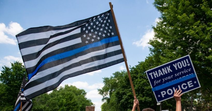 """A demonstrator holds a """"Thin Blue Line"""" flag and a sign in support of police during a protest outside the Governors Mansion on June 27, 2020, in St Paul, Minnesota."""
