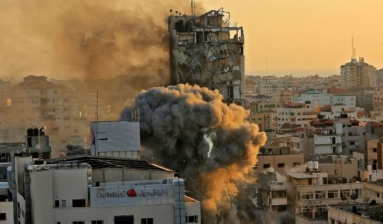 Heavy smoke and fire rise from Al-Sharouk tower as it collapses after being hit by an Israeli air strike in Gaza City on Wednesday.