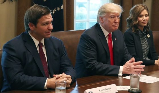 Republican Florida Gov. Ron DeSantis, left, sits next to former President Donald Trump during a meeting in the Cabinet Room at the White House on Dec. 13, 2018, in Washington, D.C.