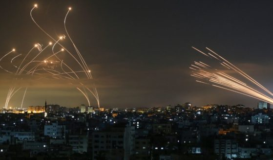 The Israeli Iron Dome missile defense system, left, intercepts rockets, right, fired by Hamas toward southern Israel from Beit Lahia in the northern Gaza Strip as seen in the sky above the Gaza Strip overnight on Friday.