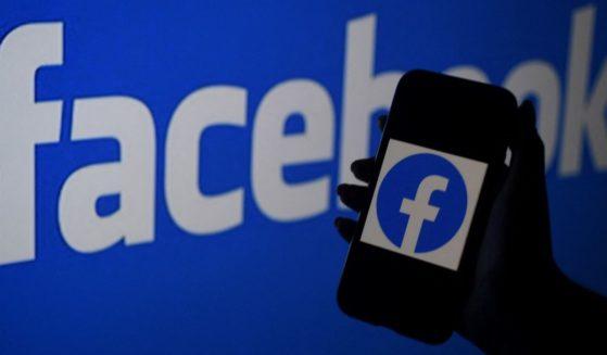 A smartphone screen displays the logo of Facebook on a Facebook website background on April 7 in Arlington, Virginia.
