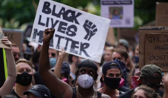 "Protesters hold a ""Black Lives Matter"" sign and raise their fists as they march through Greenwich Village in a demonstration over the death of George Floyd on June 19, 2020, in New York."