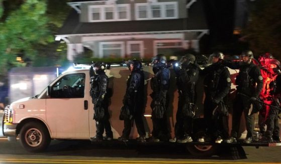 Portland police in riot gear are pictured riding on the sideboards of a police van in an Aug. 8 file photo after dispersing a mob in front of the Mutnomah County Sheriff's Office.