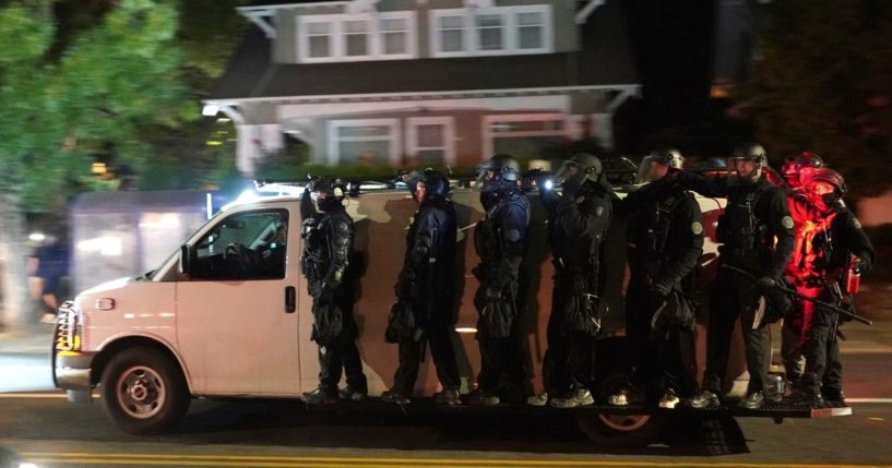 Portland police in riot gear are pictured riding on the sideboards of a police van in an Aug. 8 file photo after dispersing a mob in front of the MutnomahCounty Sheriff's Office.