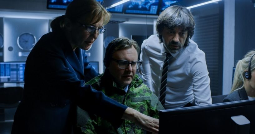 A uniformed man and two people in civilian clothes pore over a computer monitor.