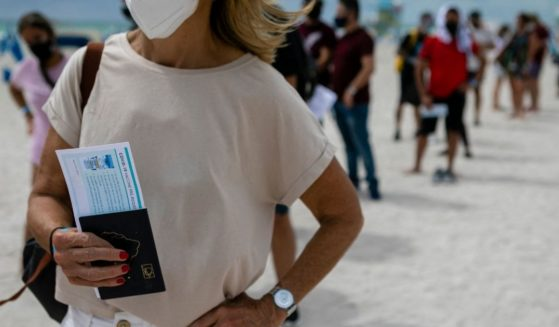 A woman holds her passport as she waits in line to get the Johnson & Johnson COVID-19 vaccine at a pop-up vaccination center at the beach, in South Beach, Florida, on May 9, 2021.