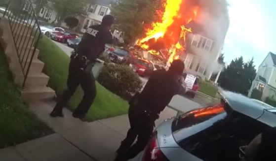 Police in Baltimore County, Maryland, draw their weapons upon arriving on the scene of a fire and shooting in Woodlawn on May 8.