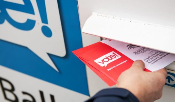 A man places a mail-in ballot in a drop box in the above stock image.