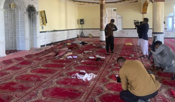 Afghan journalists take photos and film inside a mosque after a bomb explosion in Kabul, Afghanistan, on Friday.