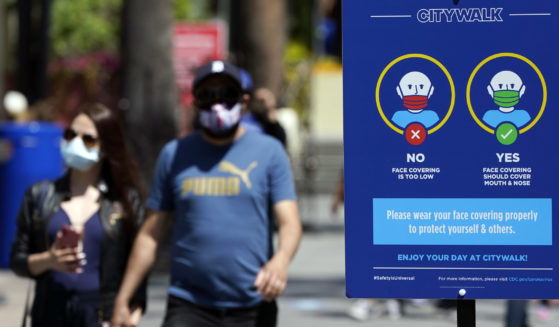In this Friday photo, signs instruct visitors on the proper way to wear masks at the Universal City Walk in Universal City, California.