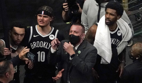 A security guard points as Brooklyn Nets' Kyrie Irving, right with towel, and teammates look up at a fan who reportedly threw a water bottle at him as he left the court after Game 4 during an NBA basketball first-round playoff series on Sunday in Boston.