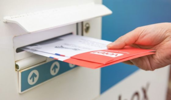 A man places ballots in a drop box in the above stock image.