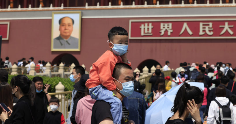 In this May 3, 2021, file photo, a man and child wearing masks visit Tiananmen Gate near the portrait of Mao Zedong in Beijing.