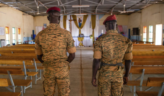 Two soldiers stand in a Catholic church at army barracks in Kaya, Burkina Faso, on April 10, 2021.