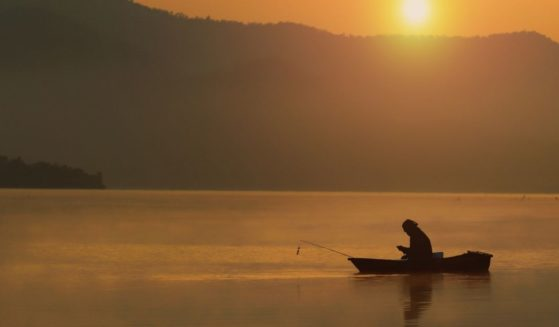 A fisherman fishing on a lake at sunset is seen in the stock image above. One lone fisherman helped rescue a 10-year-old who couldn't swim and fell out of his kayak on Sunday in New York.