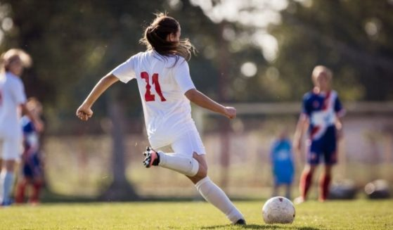 A girl plays soccer in this stock image.