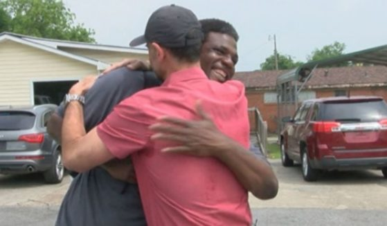 Jamie, a homeless man, and Al, a man who helped him, hugging.