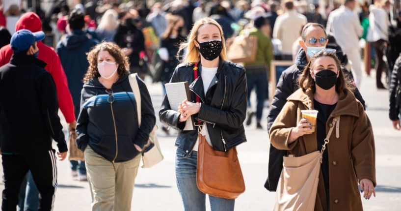 People wear face masks outdoors on March 10, 2021, in New York City.