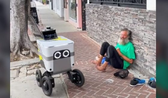 A food delivery robot rolls past a barefoot bearded man sitting on a sidewalk in Los Angeles in a video posted to TIkTok last week.