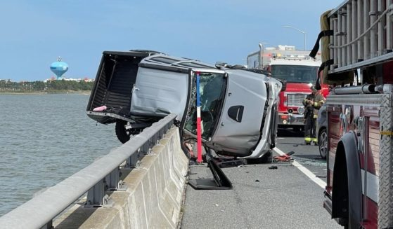 A truck teeters on the edge of a guardrail after a car accident