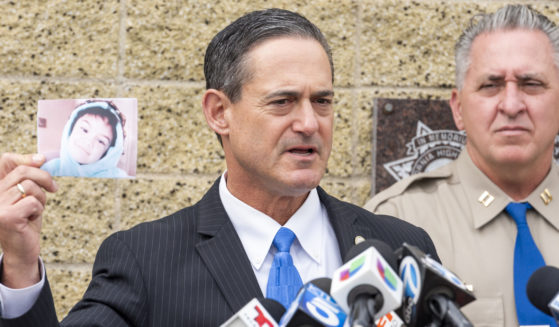 Orange County District Attorney Todd Spitzer holds up a photo of Aiden Leos during a news conference outside in Santa Ana, California, on Monday.