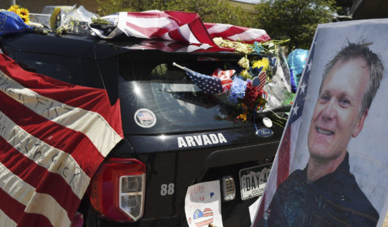 Flowers, flags and notes cover a patrol car and bike outside Arvada City Hall during a memorial for Arvada police officer Gordon Beesley on Tuesday in Arvada, Colorado.