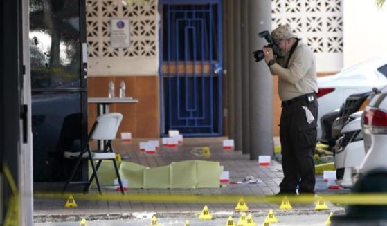 Miami-Dade police officers work the scene of a shooting outside of a banquet hall near Hialeah, Florida, on Sunday.