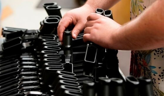 A worker places pistol grips for an AR-15 style rifle on a cart at Davidson Defense in Orem, Utah, on Feb. 4, 2021.