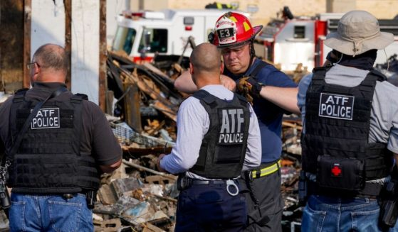 ATF agents look over the damage at an office supply company that was burned during a protest Tuesday, Aug. 25, 2020, in Kenosha, Wisconsin