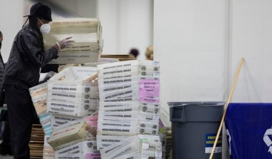 A worker with the Detroit Department of Elections helps stack empty boxes used to organize absentee ballots after nearing the end of the absentee ballot count at the Central Counting Board in the TCF Center on Nov. 4, 2020, in Detroit.