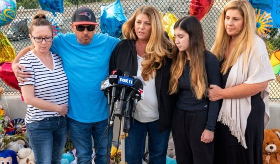 In this May 25 file photo, family members of 6-year-old Aiden Leos stand at a makeshift memorial on the Walnut Avenue overpass at the 55 Freeway in Orange, California, to announce that the reward for information leading to the suspects in the road-rage shooting death of Leos. Family members and friends tearfully remembered Leos, who was shot and killed in the incident on a Southern California freeway, at his memorial service on Saturday.