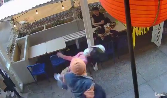 An Asian woman is punched in the face as she walks by a restaurant in Chinatown in New York City on Monday.