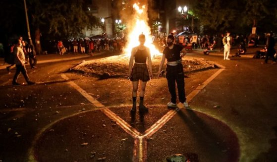 Demonstrators draw a peace sign in front of a fire during a Black Lives Matter protest at the Mark O. Hatfield United States Courthouse on July 28, 2020, in Portland, Oregon.