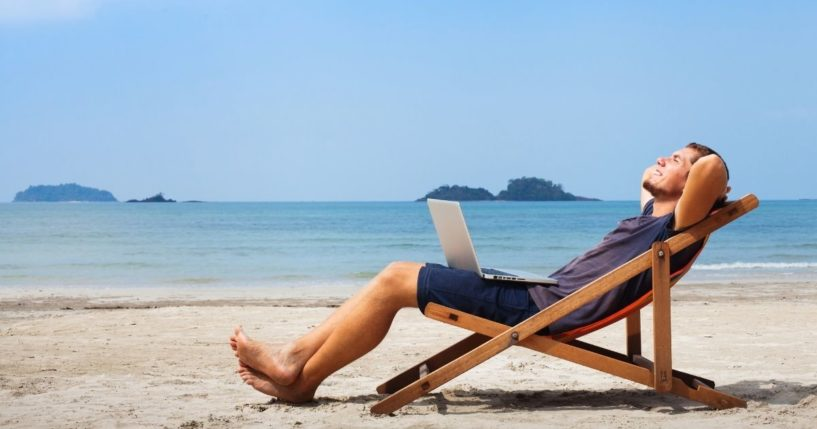 Happy businessman is pictured with his laptop relaxing on the beach.