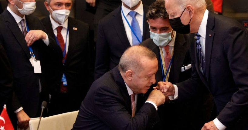 Turkey's President Recep Tayyip Erdogan fist bumps with President Joe Biden as he stands up to greet him during a plenary session at a NATO summit in Brussels on Monday.
