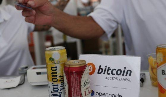 """Un letrero de """"Bitcoin aceptado aquí"""" se encuentra en la barra durante la Convención Bitcoin 2021, una conferencia sobre criptomonedas celebrada en el Centro de Convenciones Mana en Wynwood el viernes en Miami, Florida."""