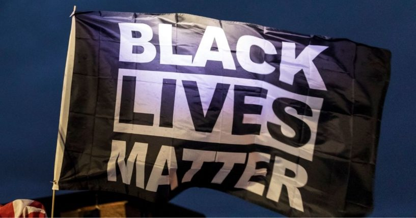 Demonstrators fly a Black Lives Matter flag outside the Brooklyn Center police station in Brooklyn Center, Minnesota on April 14, 2021.