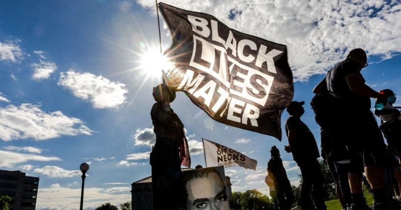 A woman holds a Black Lives Matter flag during an event in remembrance of George Floyd outside the Minnesota State Capitol on May 24, 2021, in Saint Paul, Minnesota.