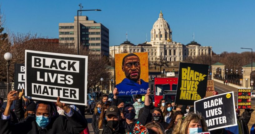 """Protesters hold signs during the """"Justice for George Floyd"""" march at the Minnesota State Capitol on March 19, 2021, in Saint Paul, Minnesota."""