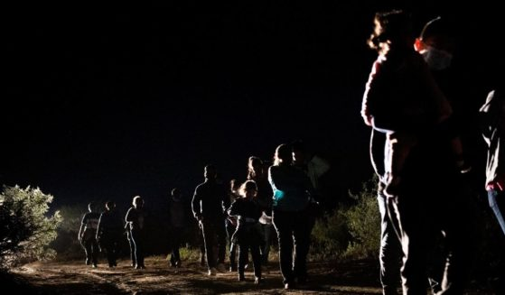 Immigrants seeking asylum walk to be processed at a border patrol processing facility after crossing the Rio Grande into the United States on Thursday in Roma, Texas.