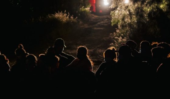 Immigrants seeking asylum wait to be accounted for and taken to a border patrol processing facility after crossing the Rio Grande into the U.S. on Saturday in Roma, Texas.