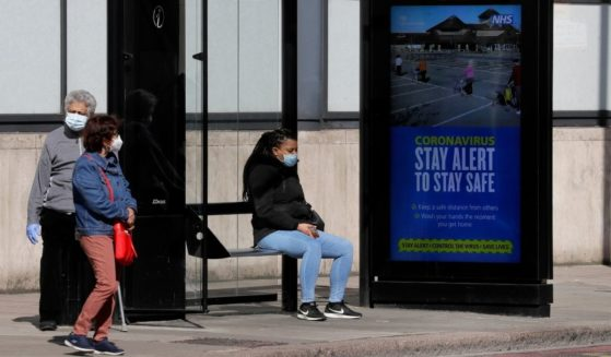 People wait at a bus stop in London on May 12, 2020.