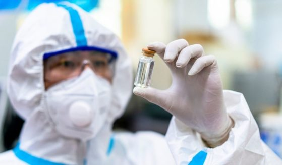 This stock photo portrays a lab worker holding up a bottle filled with clear liquid. Ivermectin, an FDA-approved antiparasitic drug, may be useful in the treatment of COVID-19.