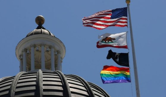 The rainbow Pride flag flutters below the U.S. and California flags at the state Capitol in Sacramento on June 17, 2019.