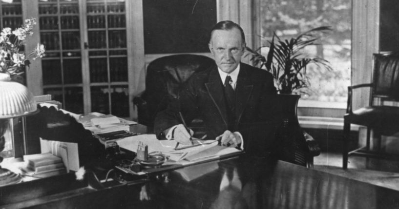 Former President Calvin Coolidge sits at his desk in the White House, in Washington D.C., on Aug. 15, 1923.